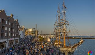 Poole Quay with crowds, motorcycles and a tall ship alongside Quay.